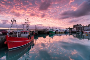 Beautiful sunrise over fishing boats in the harbour at Padstow in Cornwall